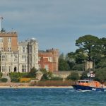 The Fraser Lifeboat leaving Poole Harbour with Brownsea Castle visible in the background